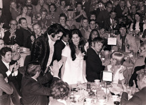16 Jan 71 - Photo by Dave Darnell.  Elvis Presley (cq) and wife, Priscilla (cq) stand as he is introduced at a luncheon at the Holiday Inn Rivermont.  Presley was being honored by the Jaycees of America as one of the Outstanding Young Men In America.  Seated at left fore and applauding is William N. Morris (cq), former sheriff of Shelby County.  Seated and applauding to right of Priscilla (and staring at camera) is Red West.