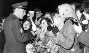 4th March 1960, Prestwick, Scotland, Sergeant Elvis Presley, American rock and roll singer, meets some of his screaming teenage fans who are there to greet him following his demobilization from the United States Army  (Photo by Popperfoto/Getty Images)