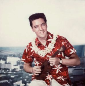 American rock n' roll singer Elvis Presley plays a ukelele, wearing a Hawaiian shirt and lei, in a still from the film 'Blue Hawaii,' directed by Norman Taurog, 1961. (Photo by Paramount Pictures/Courtesy of Getty Images)