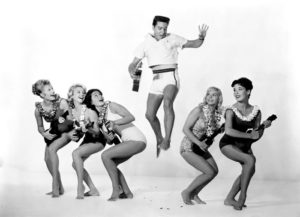 ca. 1961 --- Cast members of  from left: Pamela Austin as Selena Emerson, Darlene Tompkins as Patsy Simon, Joan Blackman as Maile Duval, Elvis Presley as Chad Gates, Jenny Maxwell as Ellie Corbett, and Christian Kay as Beverly Martin. --- Image by © John Springer Collection/CORBIS