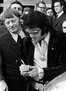 16 Jan 1971 - Photo by Dave Darnell.  Elvis Presley (cq) signs autographs for fans after leaving a luncheon at the Holiday Inn Rivermont.  At left is Red West (cq).  Behind West is William N. Morris (cq), former sheriff of Shelby County.  Presley was being honored by the Jaycees as one of the Outstanding Young Men In America.  This photograph appeared on Page One of The Commercial Appeal when Presley died in 1977.